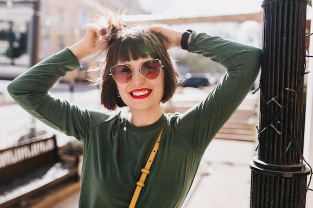 Wesoła biała dziewczyna z beztroskim uśmiechem pozowanie na ulicy. modna kobieta bawi się swoimi czarnymi włosami, wygłupiając się na świeżym powietrzu.