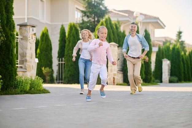 Wesoła biegająca mała dziewczynka i doganiająca rodziców