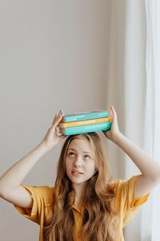 Wesoła blond dziewczyna balansująca książkami na głowie