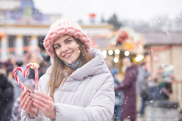 Wesoła blond kobieta nosi różowy kapelusz i szary płaszcz trzymając cukierki na ulicy christmas fair podczas opadów śniegu. miejsce na tekst