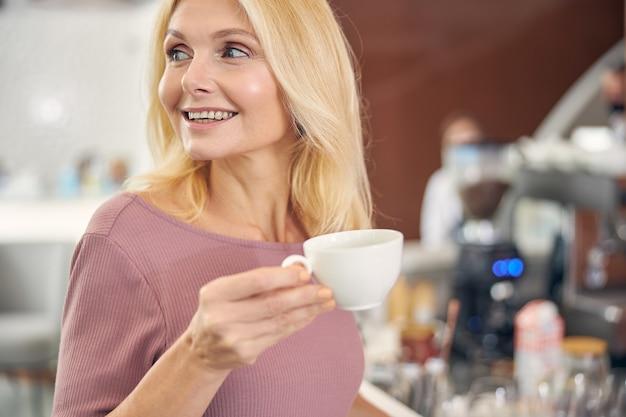 Wesoła blond kobieta trzymająca uśmiech na twarzy, patrząc z boku na okno