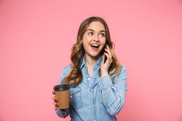 Wesoła blond kobieta ubrana w dżinsową koszulę, pijąca kawę i rozmawiająca przez smartfona, odwracając wzrok