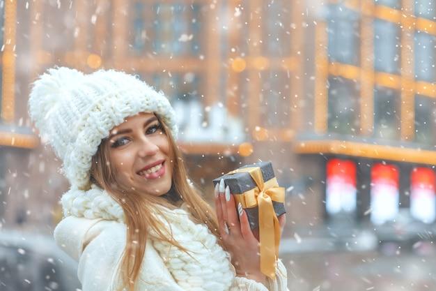 Wesoła blond kobieta w białym płaszczu, trzymając pudełko na ulicy podczas opadów śniegu podczas opadów śniegu. miejsce na tekst