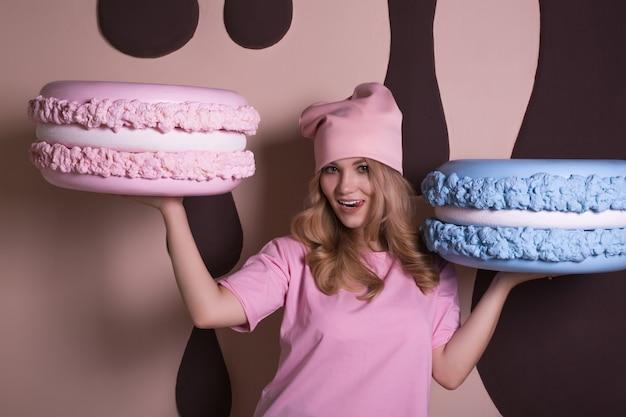 Wesoła blond modelka w różowej koszulce i czapce, trzymająca duży smaczny makaronik z ciastem