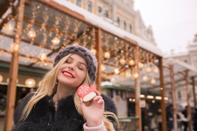Wesoła blond modelka z zamkniętymi oczami trzymająca smaczne piernikowe ciasteczko przy lekkiej dekoracji na placu w kijowie