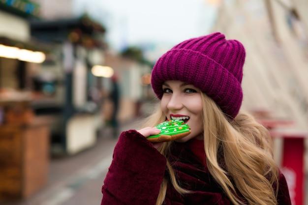 Wesoła blondynka je piernikowe ciastko, pozuje na jarmarku bożonarodzeniowym w kijowie