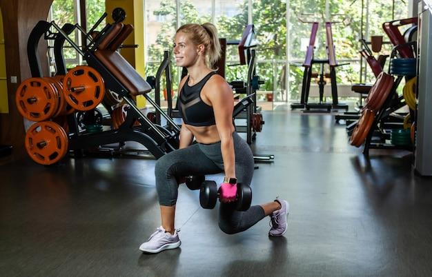 Wesoła blondynka sprawny kobieta ćwiczenia z hantlami w dłoniach. hantle rzuca się na siłownię. trening nóg