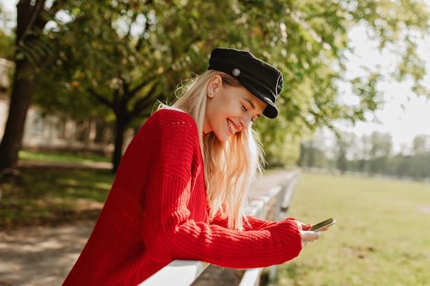 Wesoła blondynka uśmiecha się szczęśliwie w parku jesienią. ładna kobieta patrząc na swój telefon pod żółtymi drzewami.