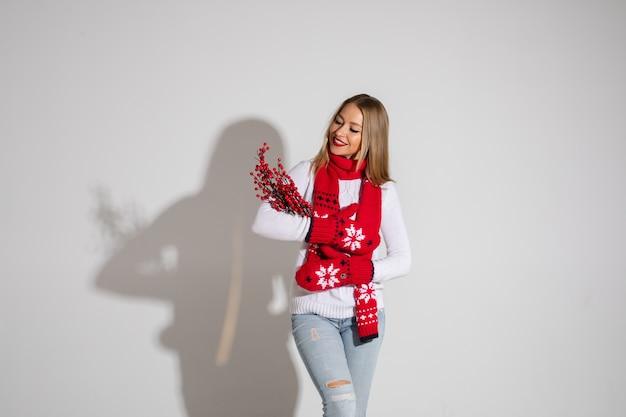 Wesoła blondynka w białym swetrze, dżinsach, czerwonym szaliku i rękawiczkach obejmująca bukiet czerwonych jagód i uśmiechająca się do nich. izoluj na białym tle.