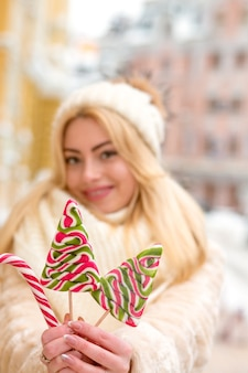 Wesoła blondynka w ciepłym kapeluszu i płaszczu, trzymająca smaczne świąteczne słodycze