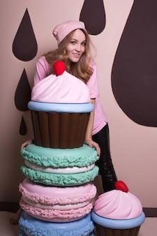 Wesoła blondynka w różowej czapce i koszulce bawi się dużymi makaronikami i babeczkami w studio