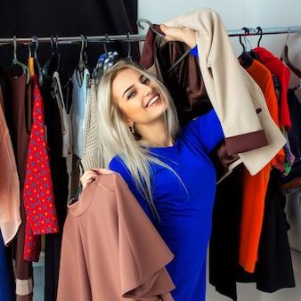 Wesoła blondynka wybiera ubrania i uśmiecha się