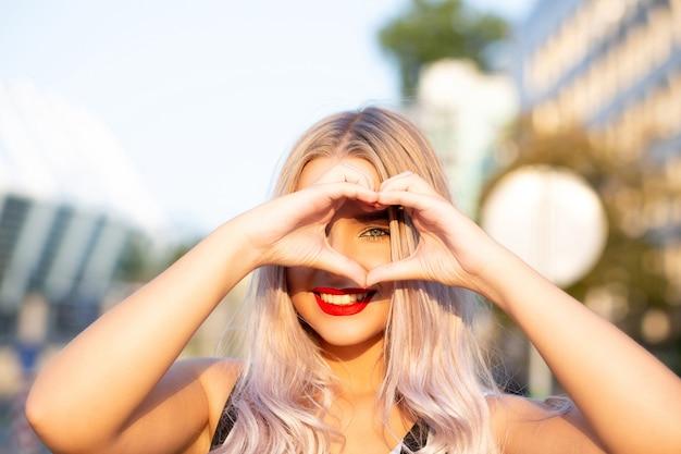 Wesoła blondynka z czerwonymi ustami robi znak serca palcami na ulicy