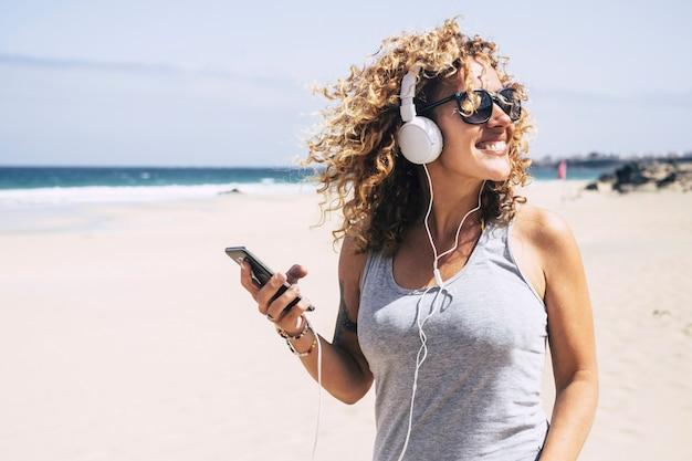 Wesoła blondynka z kręconymi włosami, ciesząc się latem na plaży, słuchając muzyki