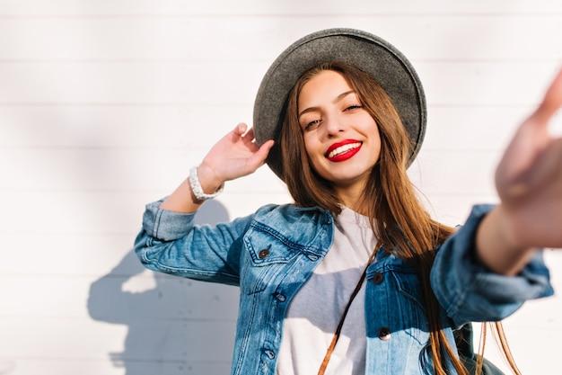 Wesoła brunetka dziewczyna w biały zegarek i szary kapelusz pozuje przed drewnianą ścianą dotykając aparatu.