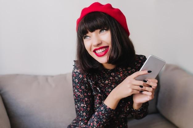 Wesoła brunetka dziewczyna w stroju retro i uroczym czerwonym berecie czeka na telefon znajomego, trzymając srebrzystego iphone'a. urocza młoda kobieta z krótkimi ciemnymi włosami, czytająca nowe wiadomości w swoim telefonie i uśmiechnięta