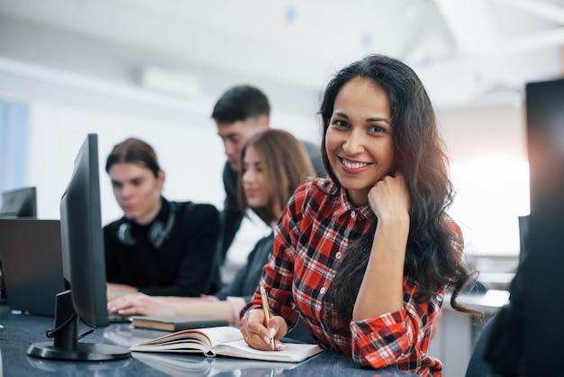 Wesoła brunetka. grupa młodych ludzi w ubranie pracujących w nowoczesnym biurze