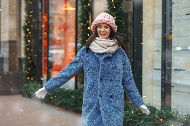 Wesoła brunetka kobieta w płaszczu ciesząc się śnieżną pogodę. pusta przestrzeń
