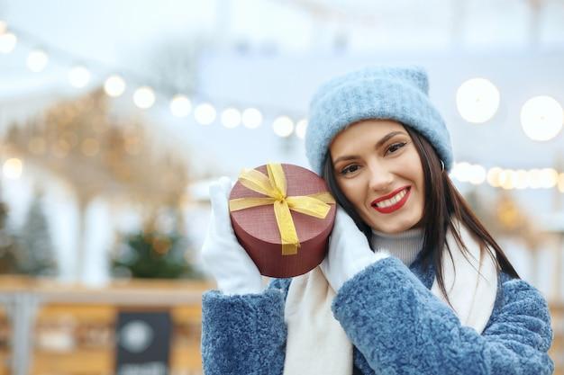Wesoła brunetka kobieta w płaszczu zimowym trzyma pudełko na targach bożonarodzeniowych. miejsce na tekst