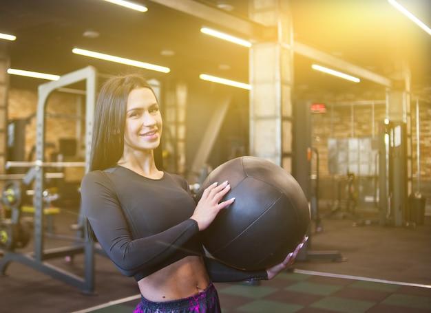 Wesoła brunetka kobieta w sportowej, trzymając w ręku piłkę lekarską i pozowanie na kamery.