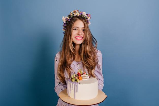 Wesoła brunetka kobieta w wieniec kwiatów z tortem urodzinowym