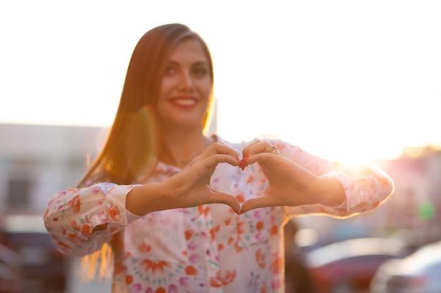 Wesoła brunetka kobieta z długimi włosami trzymająca ręce w kształcie serca na ulicy z promieniami słońca