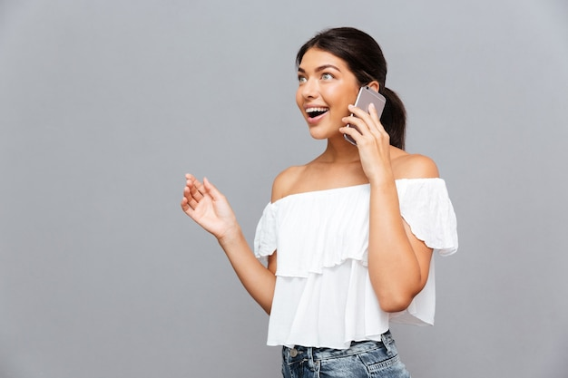 Wesoła brunetka młoda kobieta rozmawia przez telefon odizolowany na szarej ścianie