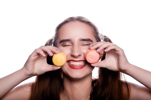 Wesoła brunetka młoda kobieta trzyma kolorowe makaroniki