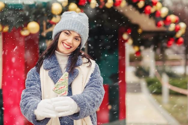 Wesoła brunetka nosi czapkę z dzianiny i płaszcz zimowy, trzymając cukierki podczas opadów śniegu. miejsce na tekst