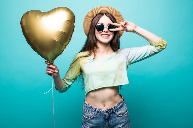Wesoła brunetka piękna pani w sukience trzyma złoty balon jak serce i pokazuje gest pokoju na białym tle