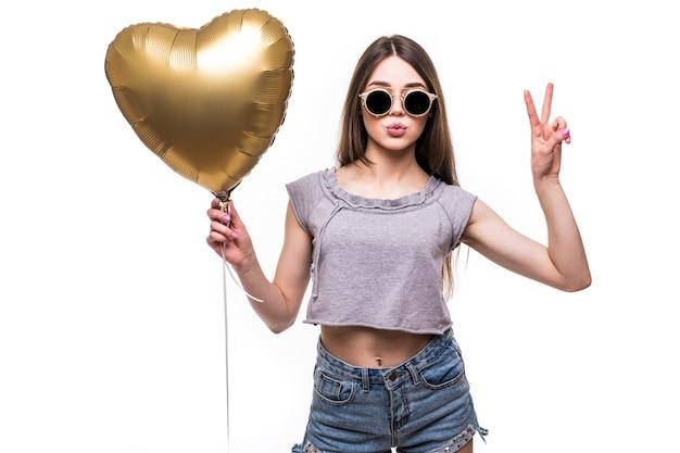 Wesoła brunetka piękna pani w sukience trzymając balon jak serce i pokazując gest pokoju na białym tle