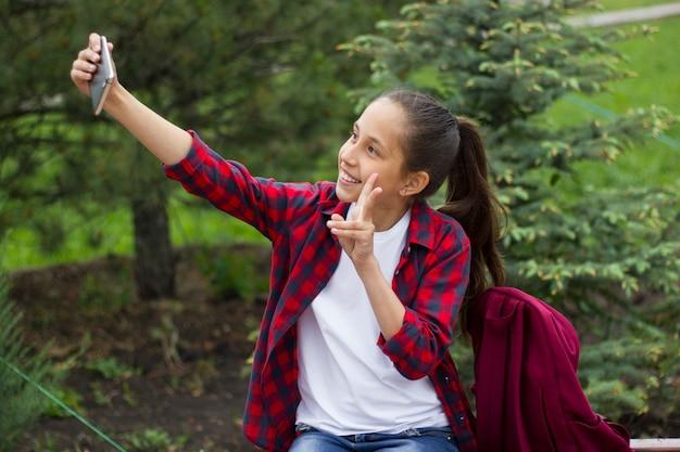 Wesoła brunetka robi selfie na telefonie komórkowym i pokazuje znak zwycięstwa