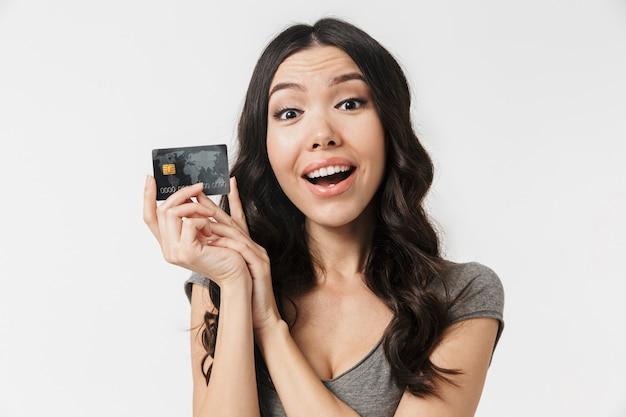 Wesoła brunetka w wieku 20 lat ubrana w podstawowe ubrania, uśmiechnięta i trzymająca kartę kredytową na białym tle nad białą ścianą