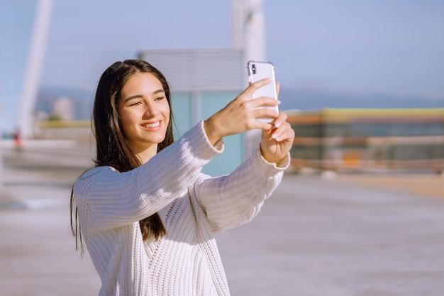 Wesoła brunetka z szerokim uśmiechem robi selfie