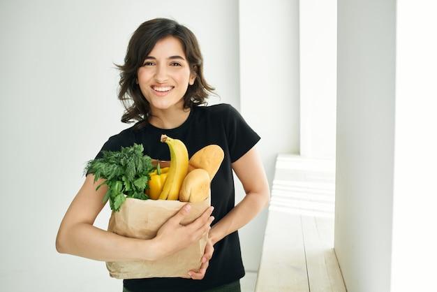 Wesoła brunetka żywności torba zdrowa żywność dostawy warzyw. zdjęcie wysokiej jakości