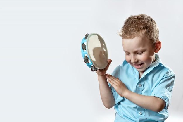 Wesoła chłopiec w niebieskiej koszuli trzyma tamburyn i uśmiechając się na jasnym tle