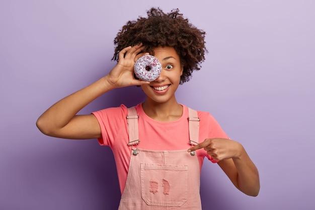Wesoła ciemnoskóra dziewczyna trzyma pączka na oku, wskazuje na siebie, jest głodna, pozuje z pysznym deserem, ubrana w stylowe ciuchy, lubi zjeść coś słodkiego, uśmiecha się radośnie, odizolowana