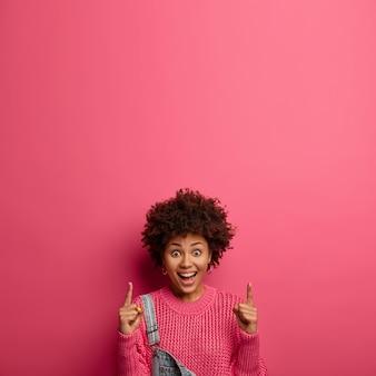 Wesoła ciemnoskóra kobieta wskazuje w górę dwoma palcami wskazującymi