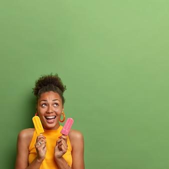 Wesoła ciemnoskóra kobieta z kręconymi, zaczesanymi włosami śmieje się radośnie, skoncentrowana powyżej, bawi się w upalny letni dzień, je pyszne lody, odizolowana na zielonej ścianie. pyszny deser