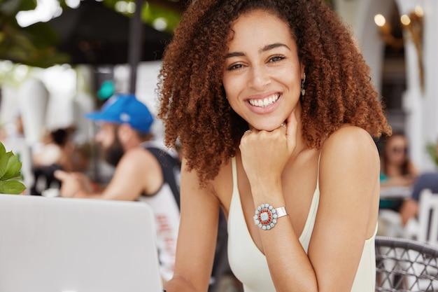 Wesoła, ciemnoskóra, radosna blogerka rasy mieszanej, odnosząca sukcesy z krzaczastą fryzurą, publikacja creats