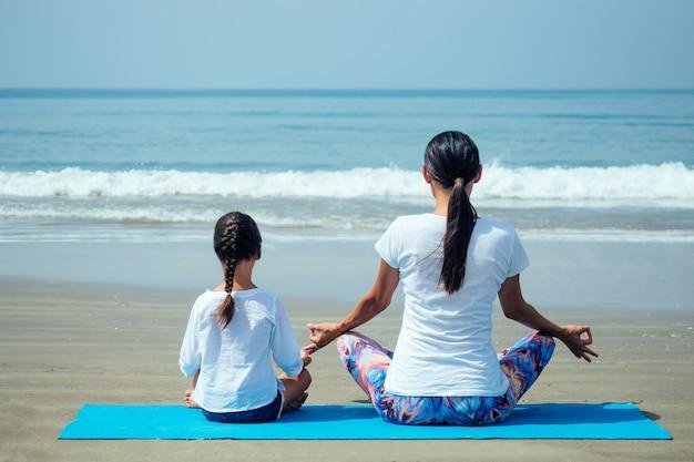 Wesoła córka i piękna mama ćwiczą jogę i wspólnie medytują na plaży.
