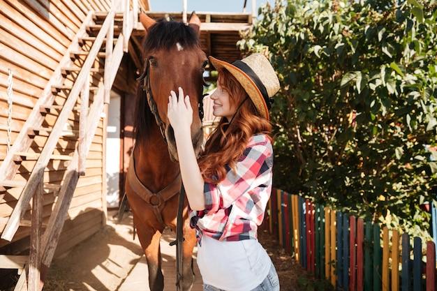 Wesoła cowgirl piękna młoda kobieta z koniem na ranczo
