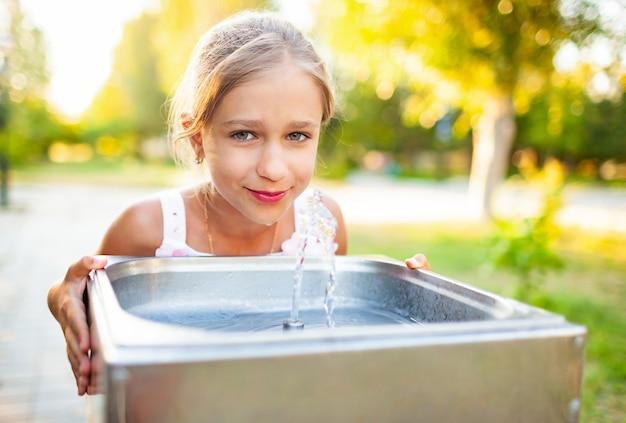 Wesoła, cudowna dziewczyna pije chłodną świeżą wodę z małej fontanny w ciepłym letnim słonecznym parku na długo oczekiwanych wakacjach