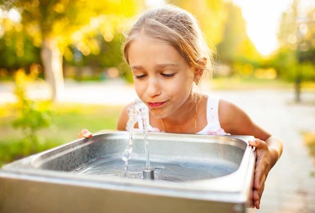 Wesoła cudowna dziewczyna pije chłodną świeżą wodę z małej fontanny w letnim ciepłym słonecznym parku na długo oczekiwane wakacje