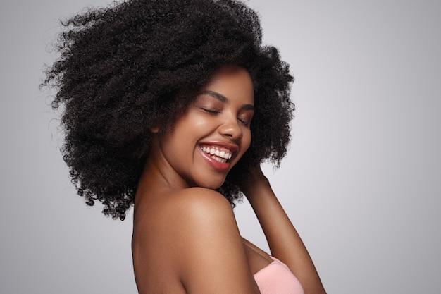 Wesoła czarna kobieta dotyka włosów