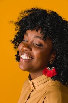Wesoła czarna kobieta śmieje się z zamkniętymi oczami