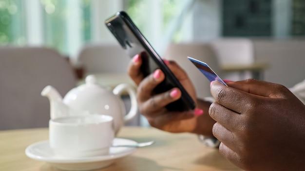 Wesoła czarna kobieta w stylowej kurtce płaci online kartą kredytową i telefonem komórkowym, siedząc przy stole z czajnikiem i filiżanką w przytulnej stołówce