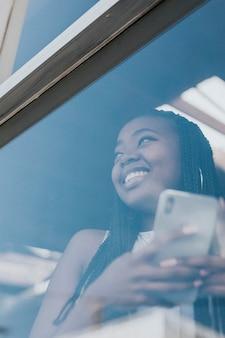Wesoła czarna kobieta wysyła sms-y na swoim telefonie