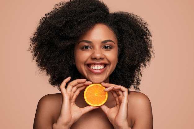 Wesoła czarna kobieta z plasterkiem pomarańczy