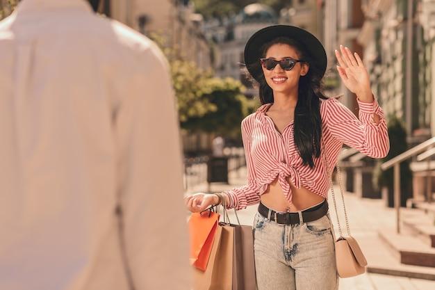 Wesoła dama w słoneczny dzień macha do mężczyzny i niesie torby z zakupami